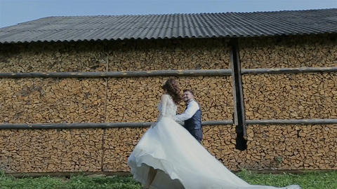 Happy bride and groom running and laughing near wooden ambar at the wedding walk Footage