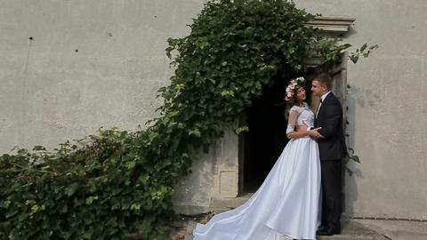 Beautiful bride and groom gently hugging in the courtyard of the old castle