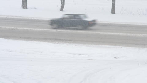 Cars passing by in winter on snow covered road Footage