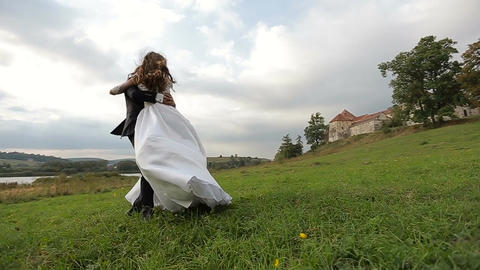 Groom turns bride on hand on the grass near the lake and the old castle