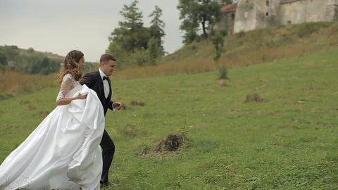 Charming wedding couple running on the grass near the lake and the old castle