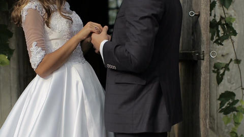 Close-up of Beautiful bride and groom gently hugging and holding hands in the co