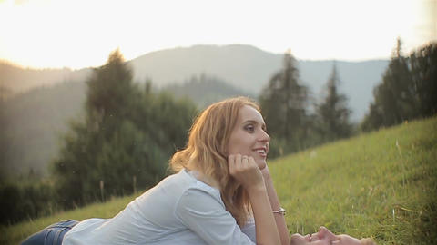 Charming couple in love have fun and lie on the grass in the mountains on sunset Live Action
