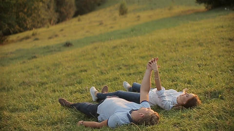 Charming couple in love and lie on the grass in the mountains on sunset Live Action
