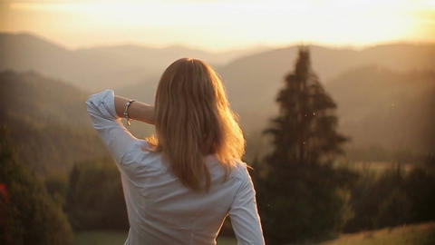 Young beautiful girl stands on the background of a beautiful sunset in the mount Footage