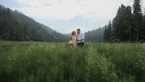 Charming couple in love hugging in the grass on the mountains background Footage