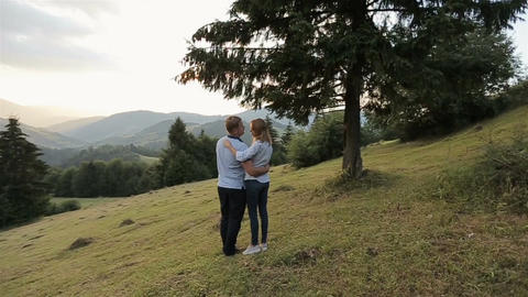 Charming couple in love hugging in the mountains on sunset Footage