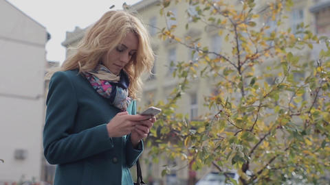 Elegant beautiful woman texting on smartphone in the city Footage