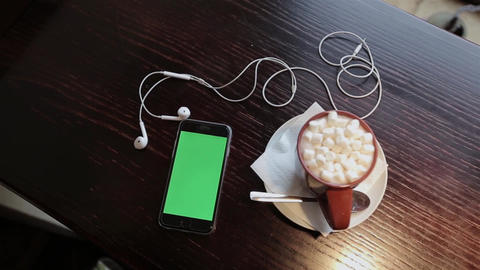 Cup of coffe with marshmellou and cellphone with green in cafe ビデオ