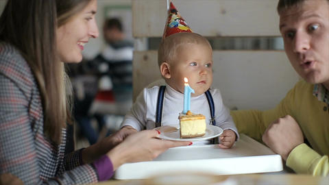 Little boy blows out candles on birthday cake at party Footage