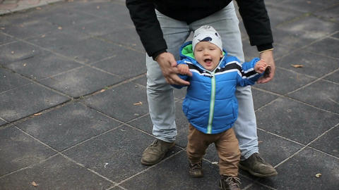 Little boy have fun with his parents at a playground Footage