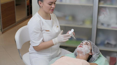 Female cosmetologist making cosmetic facial mask to the female client at the cos Footage
