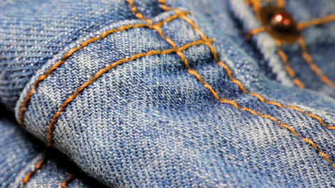 Extreme close-up tilt shot of the dark blue denim fabric of jeans with bright ye Footage