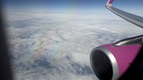 Passenger airliner flying high in sky, view through window at wing and engine Footage