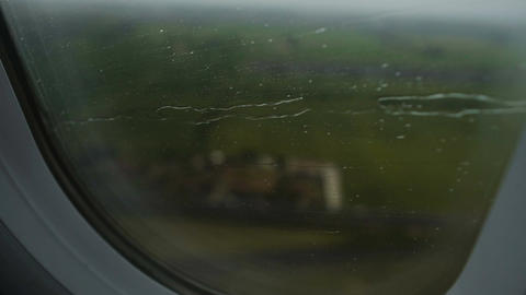 Rain water on window of passenger aircraft making emergency landing on field Footage