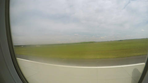 Aircraft taking off runway, gaining altitude in air, green landscape in window Footage