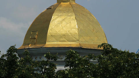 Orthodox Christian church dome topped with golden cross, cloudy sky background Footage
