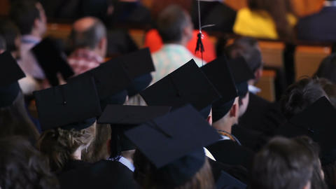 Students sitting at graduation ceremony, light balloon tied to man's mortarboard Footage