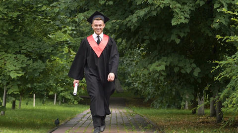 Happy male graduate walking in park, jumping with joy, success and future Footage