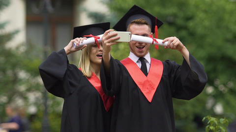 Graduate students in academic dresses taking selfies after graduation ceremony Footage