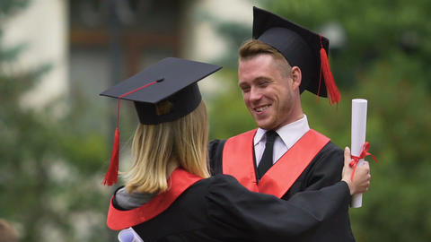 Funny graduate hugging his female friend and laughing, achievement, happy future Live Action