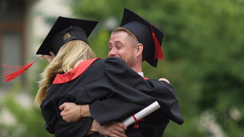 Happy couples graduates together, boyfriend carrying girl and spinning, love Footage