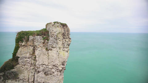 Lonely rocky cliff above endless blue sea, flying birds, serene landscape Footage