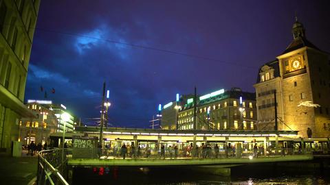 Urban life, passengers entering modern tram, brightly illuminated city center Footage