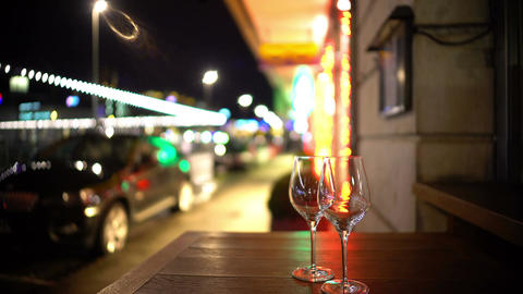 Two glasses on table in street cafe, romantic evening, restaurant business Footage