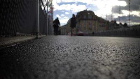 People walking across bridge, closeup view of feet on asphalt, urban life Footage