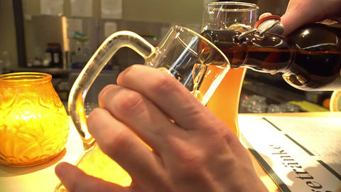 Pleased pub visitor pouring bottled beer into glass, weekend relaxation, holiday Footage