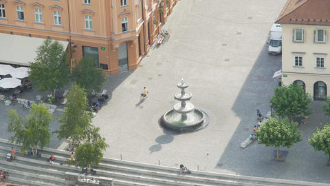 Top view of fountain in Ljubljana downtown, tourists having rest at Town Square Footage