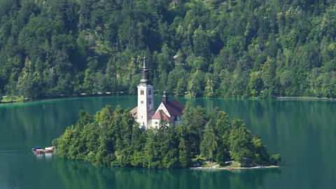 Secluded island with church surrounded by Lake Bled and Alps, spirituality Live Action
