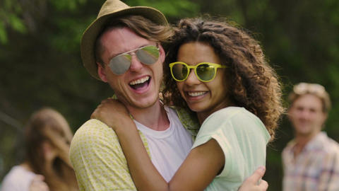 Young multiracial couple hugging, smiling and looking into camera at party Footage