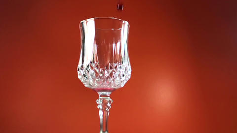 Red Wine Pouring into Glass. orange Background. Slow Motion Footage