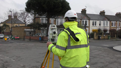 The worker measures the distance with a theodolite Footage