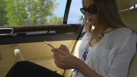 Young attractive businesswoman riding in taxi and surfing the net on smartphone Live Action