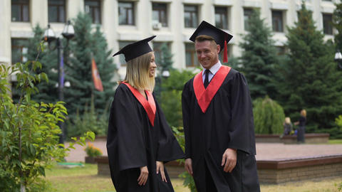 Two happy graduates relaxing in park near university and talking about future Footage