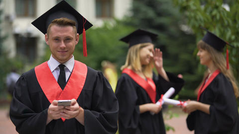 Graduate students standing in park, young man with smartphone looking at camera Footage