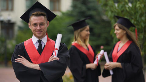 Handsome male graduate smiling for camera with folded arms, happy future Footage