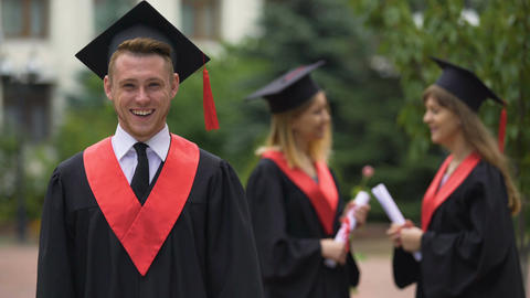 Graduation ceremony, happy man in academic dress looking into camera, laughing Footage