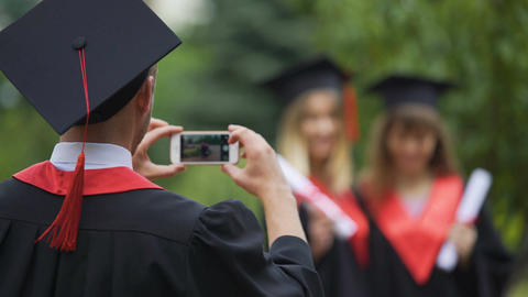 Young graduate in mantle and cap taking photos of girls on cellphone, friendship Live Action