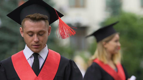 Smiling male student reading speech before graduation ceremony at university Footage