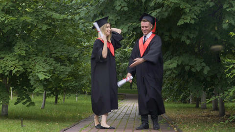 Funny graduates in academic gowns dancing and fooling around after graduation Footage