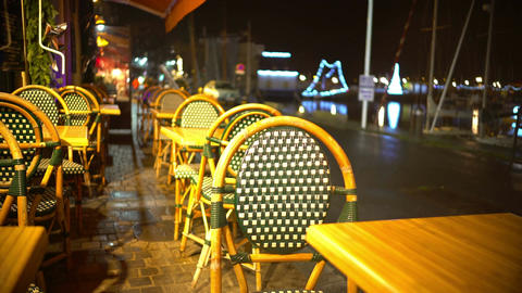 Tables and chairs of empty street restaurant, people walking by, rainy night Footage