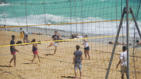 Young people enjoying volleyball game on sandy beach, team sport for friends Live Action