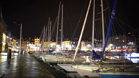 Illuminated port with parked yachts and boats, evening time in city, tourism Footage