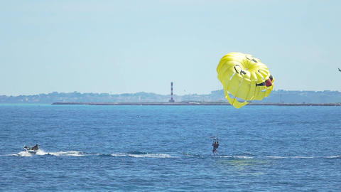 Happy people parasailing above blue sea, parachute sports, summer activities Footage