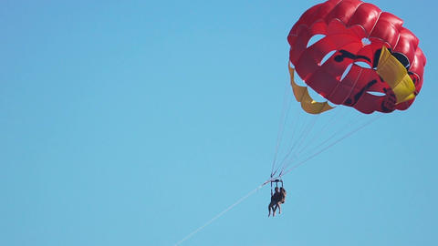 Pleased female and male athletes flying with parachute over ocean, parascending Footage
