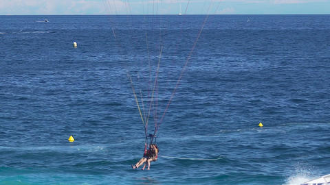 Happy woman and man falling with parachute in the sea, extreme parasailing sport Footage